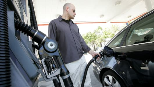 A customer pumps gasoline into his car at a service station in San Francisco.