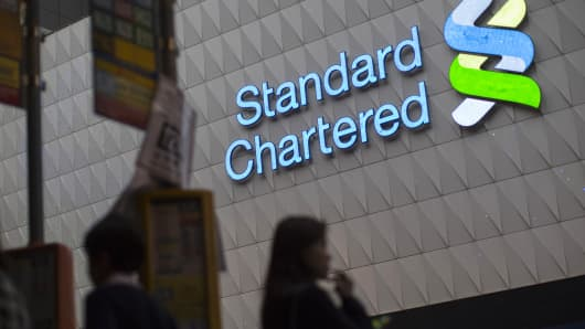 An illuminated Standard Chartered Plc logo is displayed on the Standard Chartered Bank building.