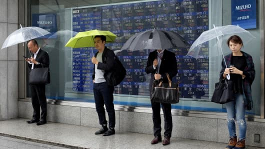 Pedestrians stand in front of a board showing share prices on the Nikkei 225 index at the Tokyo Stock Exchange in Tokyo.