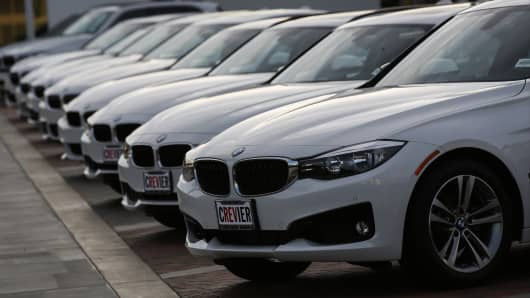 A 2014 Bayerische Motoren Werke AG (BMW) 328i xDrive Gran Turismo, right, is displayed for sale at the Crevier BMW dealership in Santa Ana, California.