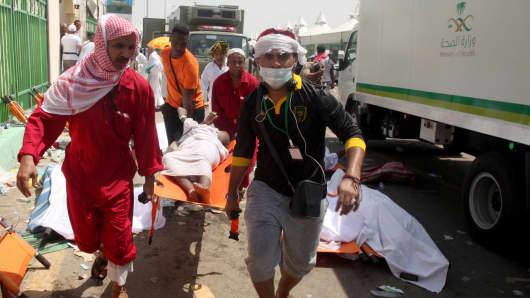 Saudi emergency personnel and Hajj pilgrims carry a wounded person at the site of a stampede in Mina, near the holy city of Mecca, at the annual hajj in Saudi Arabia on September 24, 2015.