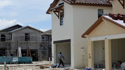 Plasterers stand on scaffolding back while a worker walks into the garage of a home under construction at the Lennar Corp. Madison Pointe at Central Park development in Doral Florida