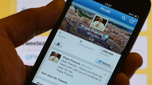 A man holds a smartphone showing Pope Francis' first tweet.