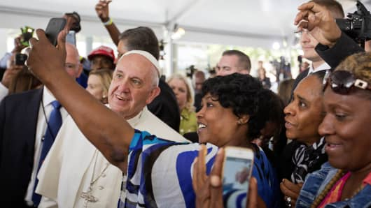 Cartrice Haynesworth, center, has a selfie taken with Pope Francis as he walks through the crowd during a visit to Catholic Charities of the Archdiocese of Washington, Thursday, Sept. 24, 2015.