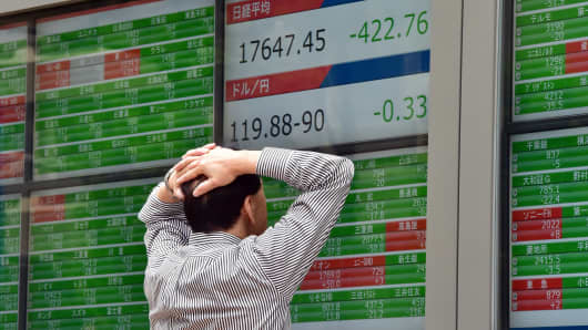A businessman watches a share price board in Tokyo, Japan.