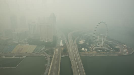 The Singapore Flyer Ferris wheel, right, stands shrouded in smog in Singapore, on Thursday, Sept. 24, 2015.