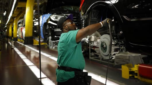 A worker uses a power tool on the wheel well of a Daimler AG Mercedes Benz M-Class vehicle at the company's international assembly plant in Vance, Alabama.