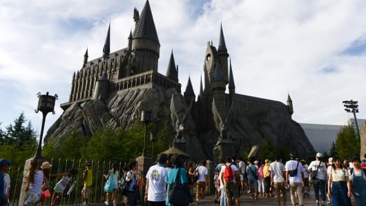 Visitors walk in front of The Wizarding World of Harry Potter themed area at Universal Studios Japan, operated by USJ Co., in Osaka, Japan.
