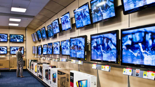 A shopper looks at televisions in a Best Buy store.