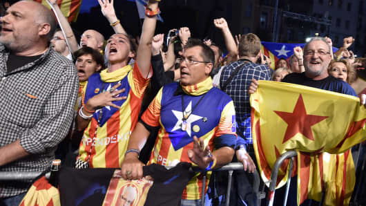 Catalan pro-indepence supporters raise their arms and wave flags following the closing of polling stations during Catalan regional election on September 27, 2015 in Barcelona.