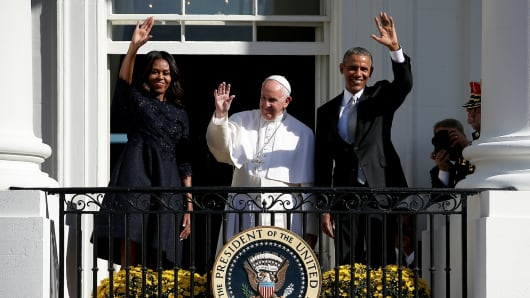 First lady Michelle Obama , Pope Francis and U.S. President Barack Obama wave from the balcony during an arrival ceremony at the White House on September 23, 2015 in Washington, DC.