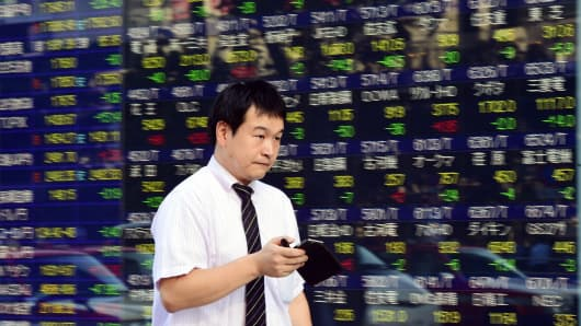 A businessman uses his smartphone before a stock price board in Tokyo, Japan.