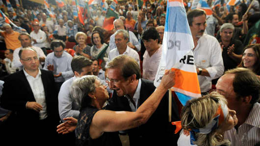 Pedro Passos Coelho, Portugal's prime minister, greets a supporter during a political rally ahead of the election in Braga, Portugal, on Sunday, Sept. 27, 2015.