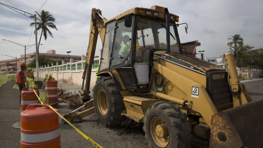 A worker operates a Caterpillar Inc. backhoe during road construction in Old San Juan, Puerto Rico.