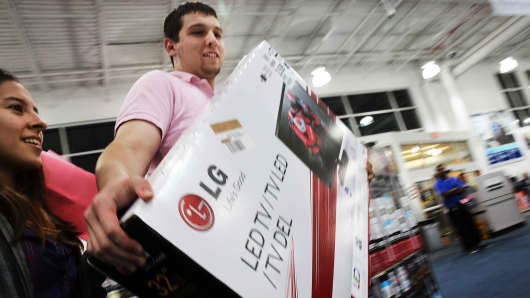 Shoppers carry away discounted items from a Best Buy store in Naples, Florida.
