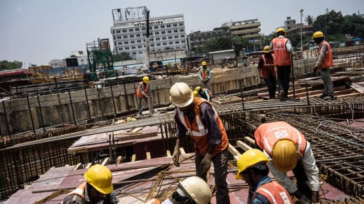 Workers prepare reinforcing steel at the construction site of the Majestic metro station in Bengaluru, India.