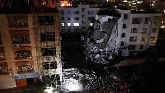 Investigators check the site of a series of blasts at a damaged building in Liucheng county in Liuzhou in south China's Guangxi province on September 30, 2015.