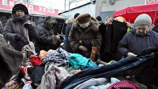 Women chose clothes at a street second hand market in St. Petersburg on December 28, 2014.