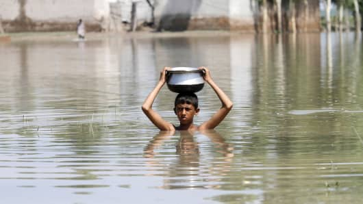 2015: A boy carries a pot on his head as he moves through floodwaters in the Pura area of Nowshera District, northwestern Pakistan