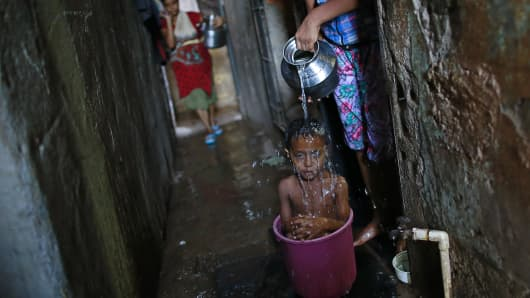 Four-year-old Manjunath takes a bath while sitting inside a bucket outside his house in a slum in Mumbai May 23, 2014.