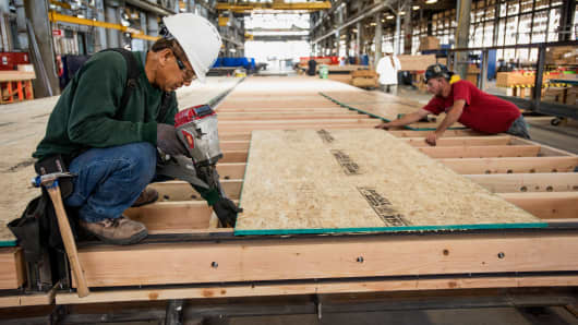 Workers assemble a floor to a house being constructed at the BLU Homes production facility in Vallejo, California, Sept. 11, 2015.