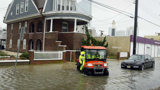 Employees drive across a street with rising flood waters, after checking a house for occupants on the north end of Atlantic City, New Jersey, October 2, 2015.