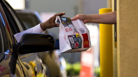 A customer receives an order from an employee at the drive-thru of a McDonald's Corp. restaurant in San Pablo, California.