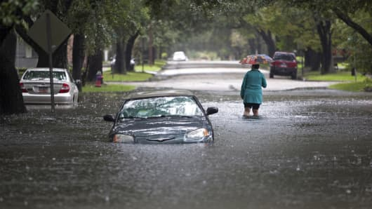 Clare Reigard of Georgetown, South Carolina, abandons her car after it stalled on Duke Street due to heavy rains in Georgetown, South Carolina October 4, 2015.