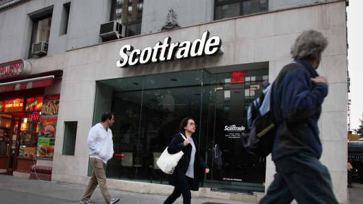 Pedestrians pass in front of a Scottrade location in New York.