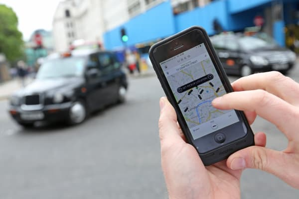 A user scans for an available vehicle using the Uber's app on a smartphone in London.