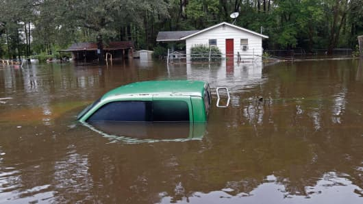 A vehicle and a home are swamped with floodwater from nearby Black Creek in Florence, South Carolina, Monday, Oct. 5, 2015.