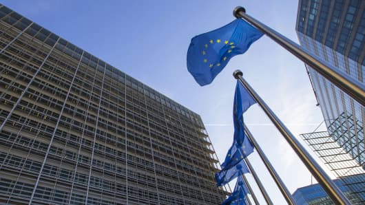European Union flags fly at the entrance of the European Commission headquarters in Brussels, Belgium.