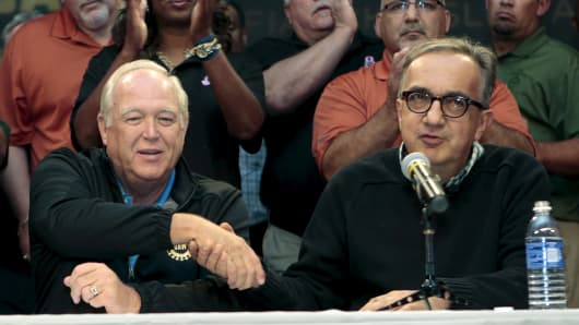Fiat Chrysler Automobiles CEO Sergio Marchionne (R) and United Auto Workers union President Dennis Williams shake hands during a news conference in Detroit, September 15, 2015.