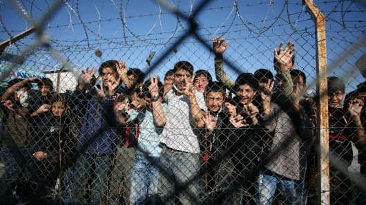 Immigrant minors peer out through the fence of an immigrant detention center in the village of Filakio, on the Greek-Turkish border.