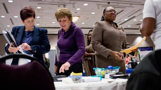 Job seekers view information at a booth during a career fair in Sterling Heights, Michigan, Sept. 30, 2015.