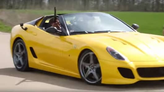 Marksman Philip Thorrold shooting at clay pigeons from the passenger seat of a rare Ferrari SA Aperta.