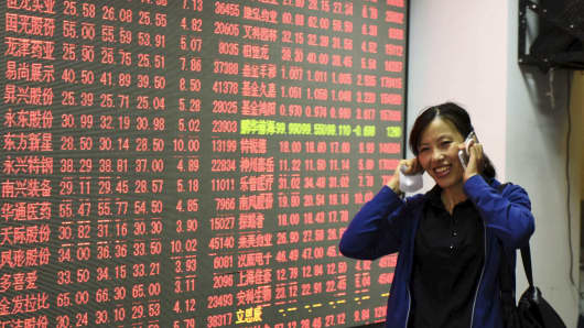 An investor speaks on her mobile phone as she walks in front of an electronic board showing stock information at a brokerage house in Hangzhou, Zhejiang province, China, October 8, 2015. China stocks posted their biggest rise in two trading weeks on Thursd