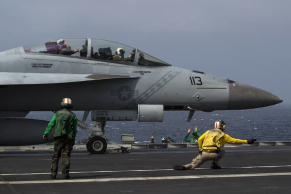 A shooter signals to the pilot of a U.S. Navy F/A-18 aircraft on the runway of the U.S. Navy aircraft carrier USS George Washington during a tour of the ship in the South China Sea. (File photo)