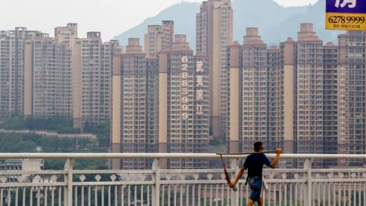 A porter walks on a bridge in Chongqing, China with new residential buildings in the background.