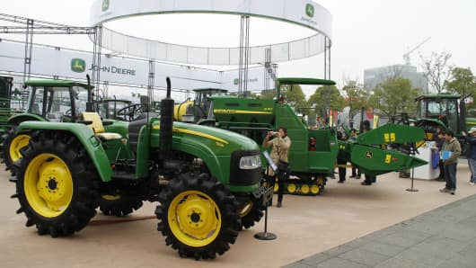 Members of the public look at tractors of John Deere at a China Jiangsu International Agricultural Machinery Exhibition (AGMA). (File photo)
