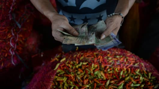 A vendor counts Indonesian rupiah banknotes near chili peppers sitting at a stall at the Pasar Induk Kramat Jati market in Jakarta, Indonesia.