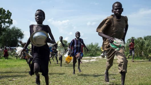 Children race into the drop zone to gather any food or seeds that were spilled during the air drop in Leer, South Sudan.
