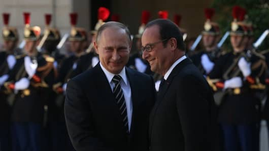 : Russian President Vladimir Putin (L) shakes hands with French President Francois Hollande (R) prior to their meeting at the Elysee Presidential Palace on October 2, 2015 in Paris, France.