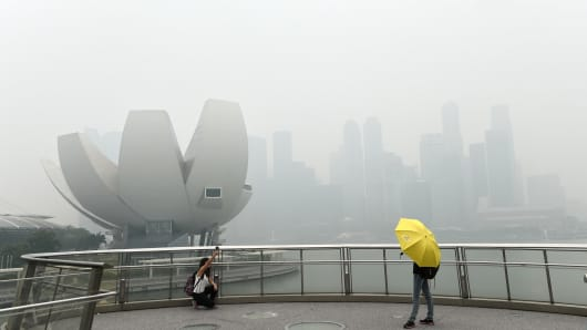 A tourist takes a 'selfie' on a bridge overlooking the Singapore skyline choked with smog on September 29, 2015.