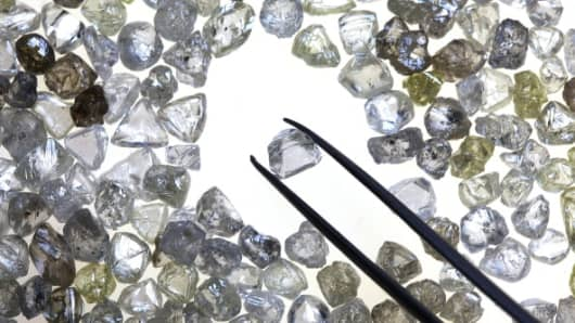 An uncut diamond is selected from a collection of colorless and colored diamonds on a sorting table at DTC Botswana, a unit of De Beers, in Gaborone, Botswana,