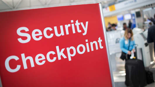 A sign directs travelers to a security checkpoint staffed by Transportation Security Administration workers at O'Hare Airport in Chicago.