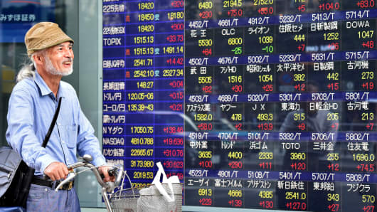 A man pushing a bicycle walks past a share prices board illustrating stocks on the Tokyo Stock Exchange in Tokyo.