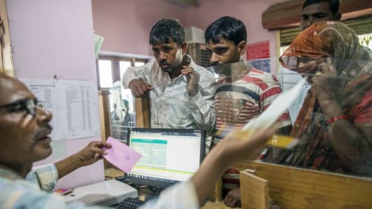 An employee serves customers inside a branch of Gramin Bank of Aryavat (GBA), sponsored by Bank of India, in the village of Khurana, Uttar Pradesh, India, on Monday, April 13, 2015.