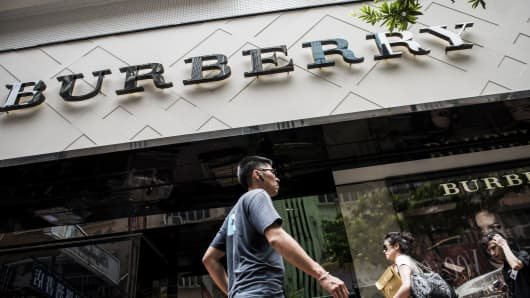 Pedestrians walk past a Burberry Group Plc store