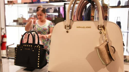 Shopper looking at Michael Kors bags at Macy's in New York.